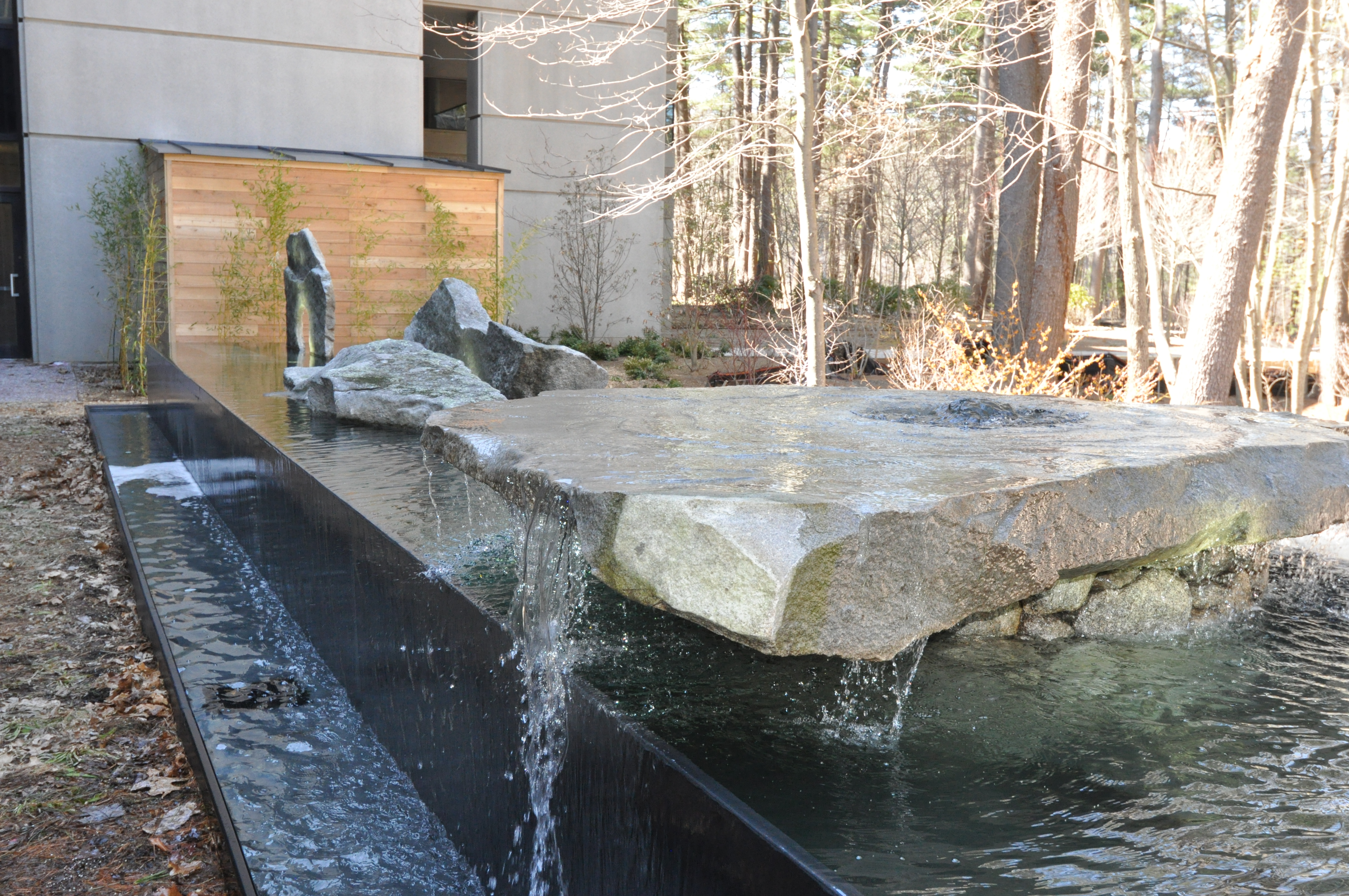 Negative edge water feature with found art stones, Oracle, Bedford MA. Design by Thomas Wirth Associates. Architectural Stones by Lew French.